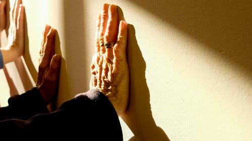 Manos de una persona mayor y una terapeuta ocupacional apoyadas en una pared