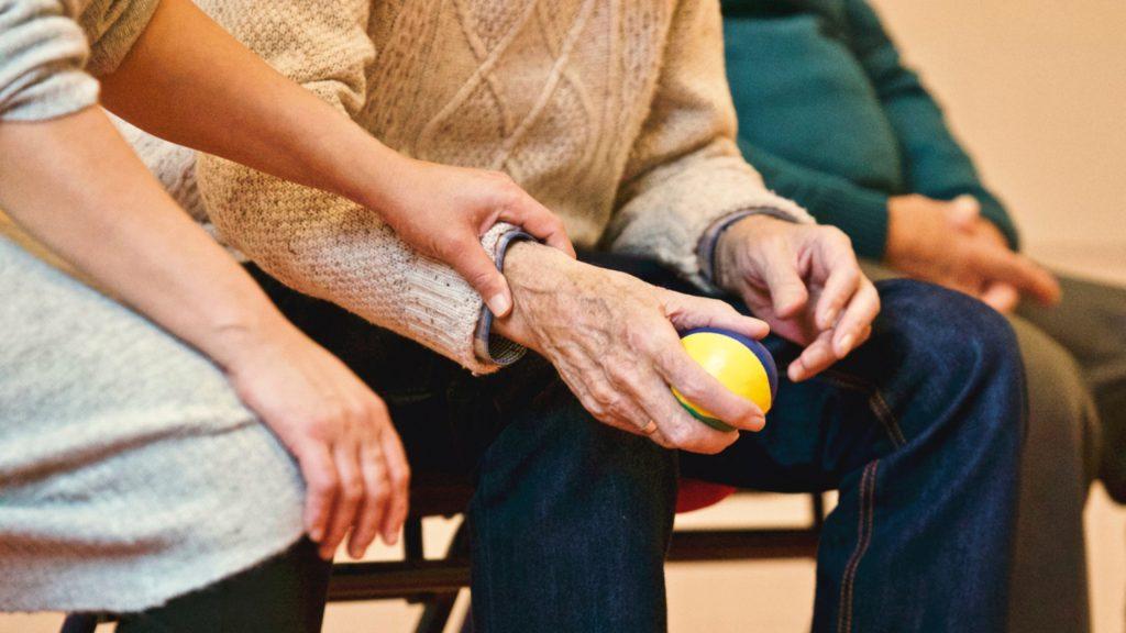 Terapeuta ocupacional cogiendo del brazo a una persona mayor que agarra una pelota